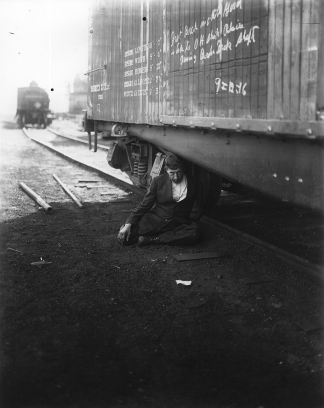 Man in suit underneath train nd