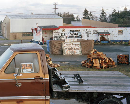 Eirik Johnson. 'Adult books, firewood and truck for sale, Port Angeles, Washington' from the series Sawdust Mountain 2006 - 2008