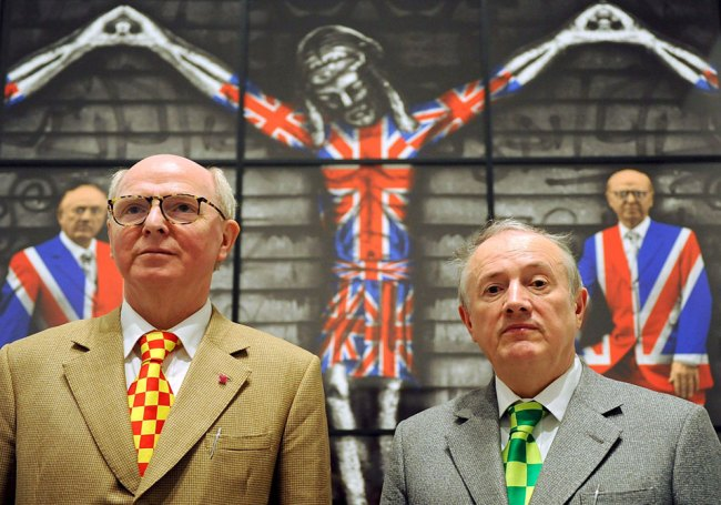"""Artist duo George (left) and Gilbert (right) pose in front of their work """"The Church of England"""" in Berlin, Germany"""