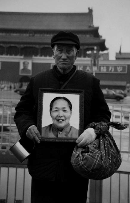 Hao Junchen. 'Hugging a portrait of his wife deceased wife, an elderly man fulfils their dream of visiting Beiijing' 2003