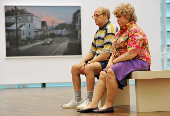 Installation photograph of the exhibition 'Duane Hanson/Gregory Crewdson: Uncanny realities' at Museum Frieder Burda with Duane Hanson 'Old Couple on a Bench' (1994) in the foreground and Gregory Crewdson 'Untitled (Worthington Street)' (2006) in the background