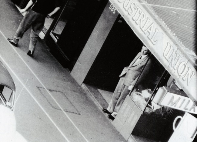 Persons Of Interest - ASIO surveillance 1949 -1980. 'Frank Hardy under awning Caption: Author Frank Hardy shelters under an awning, in the doorway of the Building Workers Industrial Union, 535 George St, Sydney, August 1955'