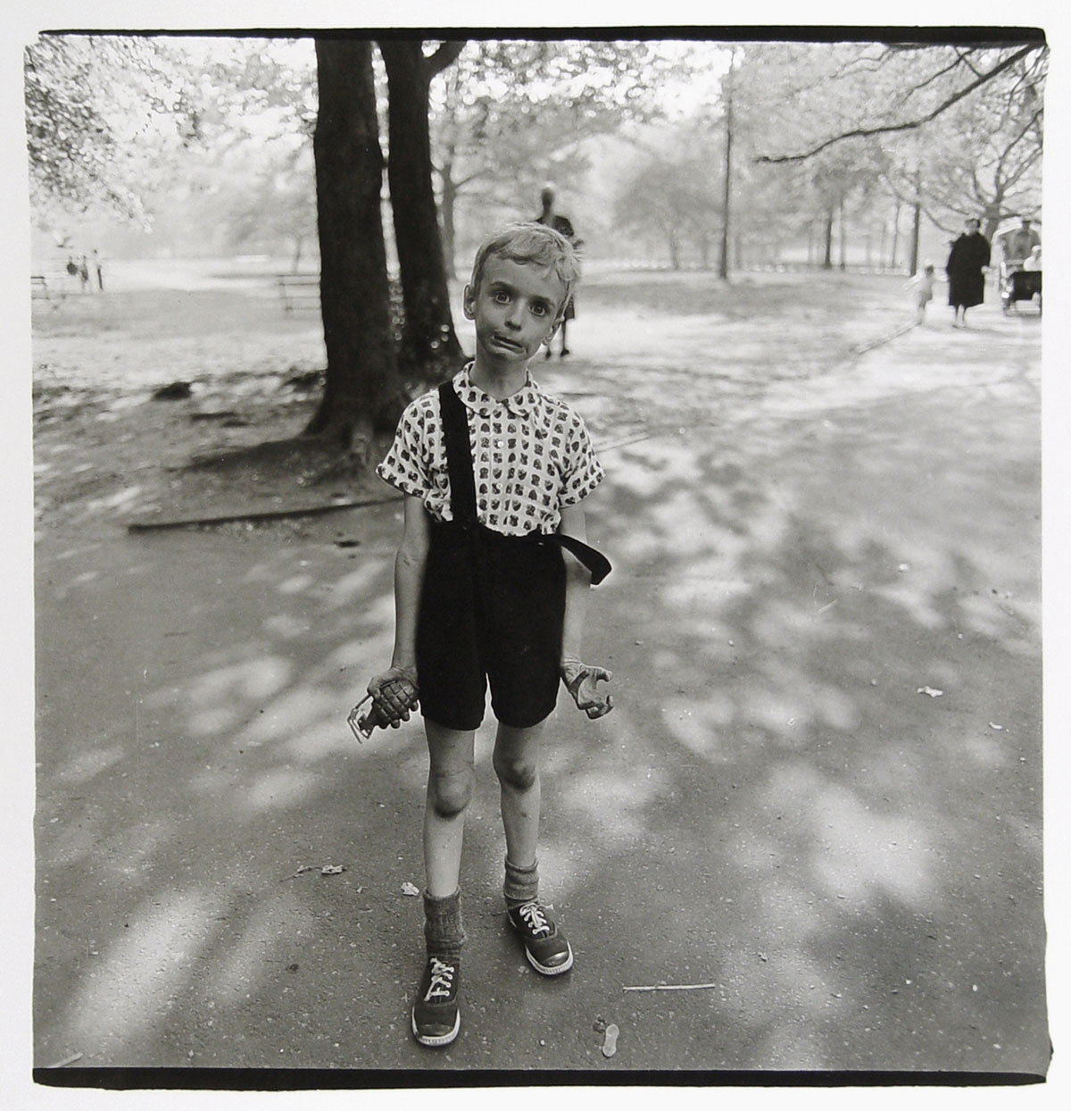 Diane Arbus photo of boy in park with toy hand grenade