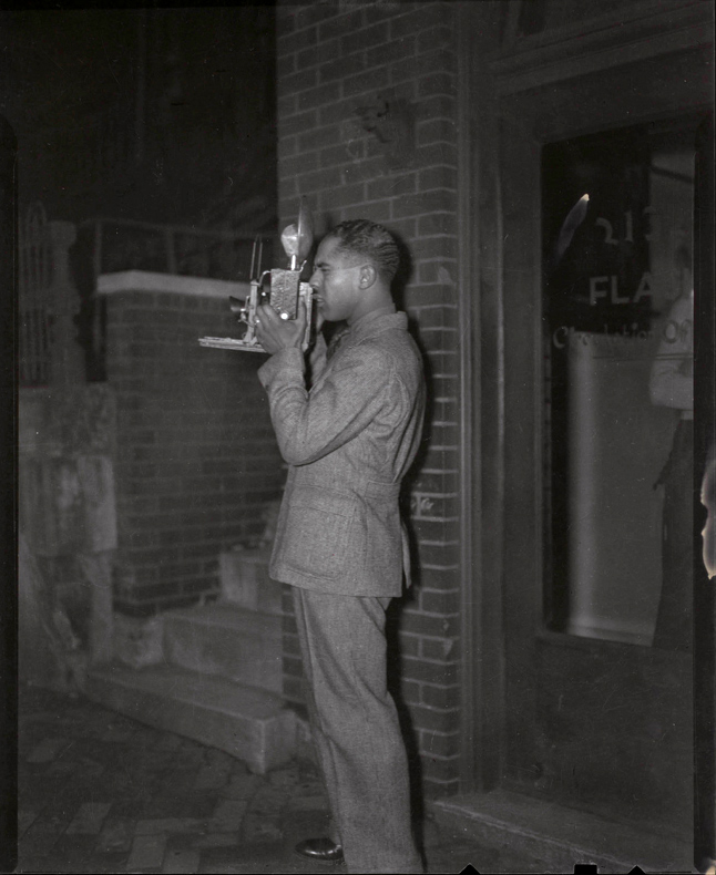 "Anonymous photographer. 'Charles ""Teenie"" Harris holding camera and standing in front of Flash Circulation office, 2132 Centre Avenue, Hill District' c. 1937"
