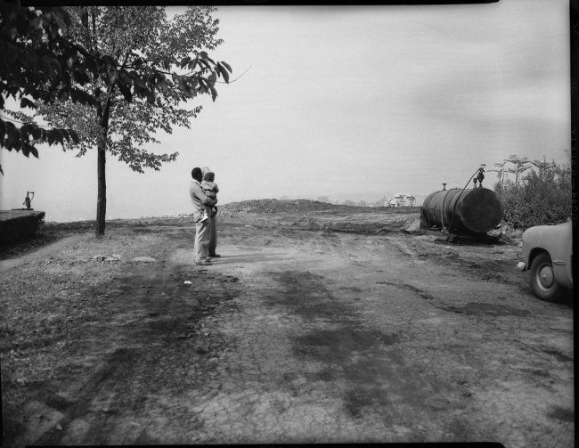 Teenie Harris. 'Construction site with bulldozer, two men, including one in front holding child, large tank with hose, and car on right, possibly in construction site of Belmar Gardens' c. 1954