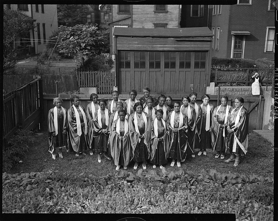 Teenie Harris. 'Group portrait of women wearing church choir robes, posed outside in yard, with other houses, garage, and woman in background, seen from above' c. 1938-1945