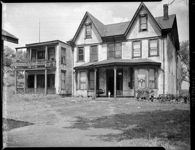 Teenie Harris. 'Large two story home with attic, porch, double entryway, and yard, with young child on steps alone, next to smaller two story home with porches on both stories' c. 1940-1945
