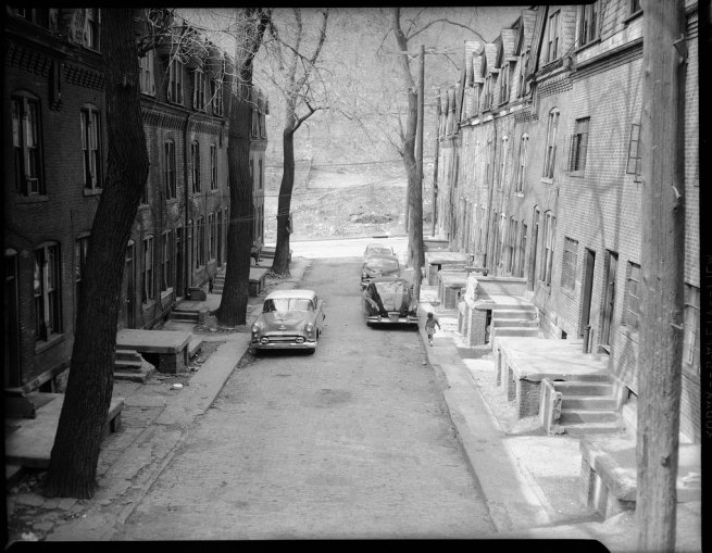 Teenie Harris. 'Three story brick row houses with mansard roofs, and small child on sidewalk of tree lined street with automobiles' c. 1958