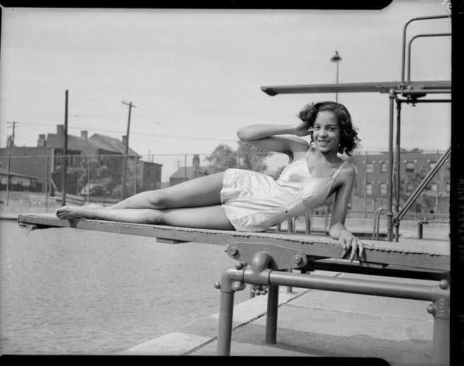 Teenie Harris. 'Woman wearing one-piece skirted bathing suit reclining on swimming pool diving board' c. 1940-1945