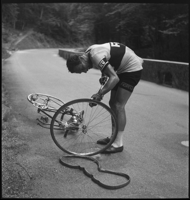 Anonymous photographer. 'Walter Diggelmann repairs a tyre during the Tour de Suisse' 1950