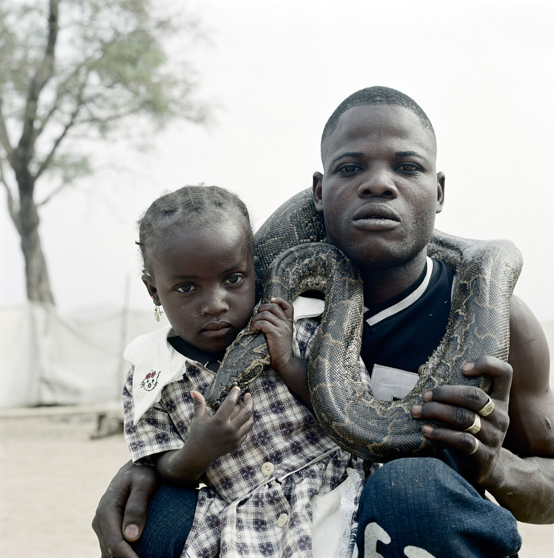Pieter Hugo. 'Mummy Ahmadu and  a snake charmer with a rock python, Abuja' From the series 'The Hyena & Other Men' 2005-2007 © Courtesy of Stevenson Gallery, Kaapstad / Yossi Milo, New York