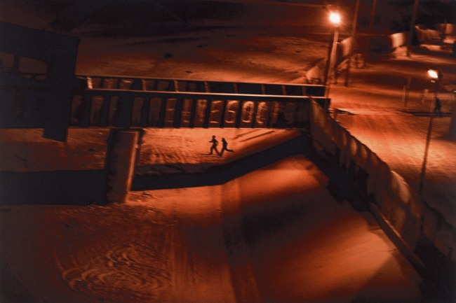 Paolo Pellegrin. 'USA. El Paso, Texas. May 17, 2011. Two men, who illegally attempted to enter the U.S., run across the dry Rio Grande river back to Juarez, Mexico after being spotted by the US Border Patrol' 2011