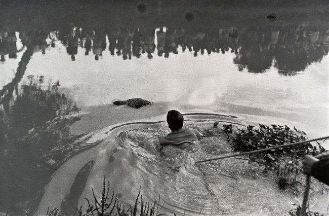 Enrique Metinides. 'Retrieval of a drowned body from Lake Xochimilco with the public reflected in the water' 1960