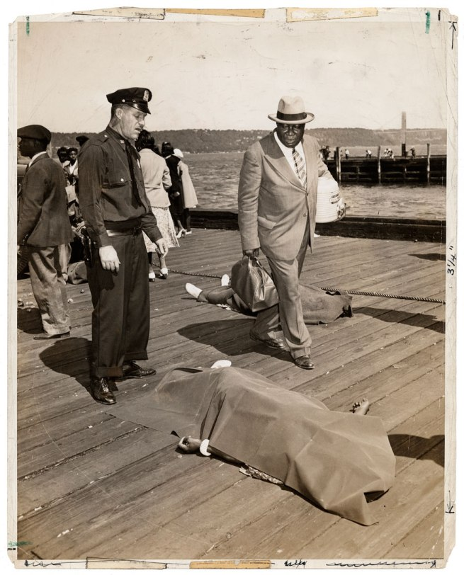 Weegee. 'Untitled [Police officer and lodge member looking at blanket-covered body of woman trampled to death in excursion-ship stampede, New York]' August 18, 1941