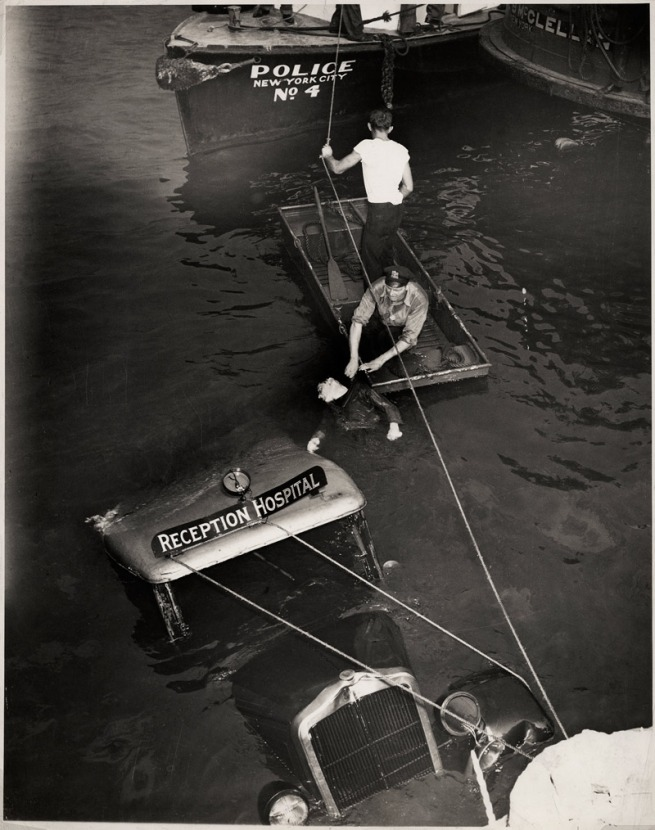 Weegee. 'Untitled [Police officer and assistant removing body of Reception Hospital ambulance driver Morris Linker from East River, New York]' August 24, 1943