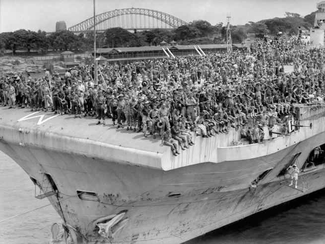 Anonymous photographer. 'Men of the 6th Division returning from Wewak crowd the deck of HMS Implacable, 18 Dec 1945' 1945
