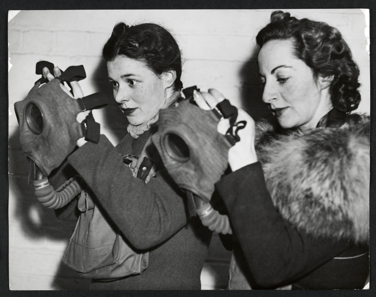 Anon. 'Two women donning gas masks as part of an air raid drill' Nd