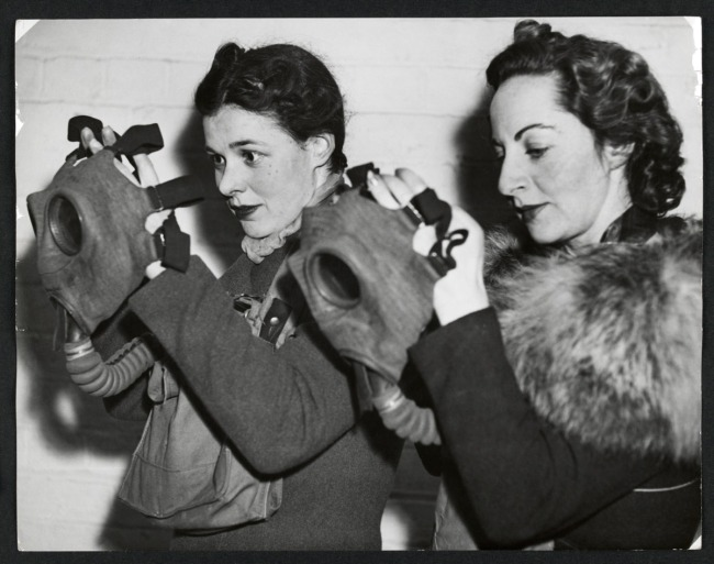 Anonymous photographer. 'Two women donning gas masks as part of an air raid drill' Nd