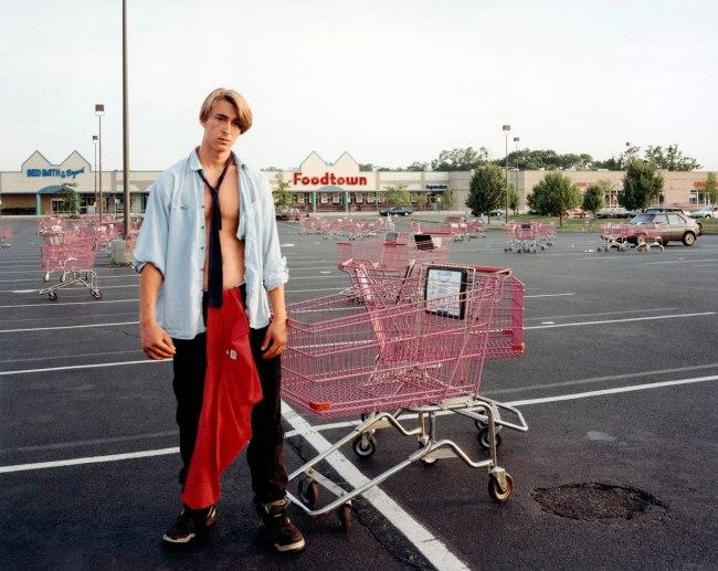 Joel Sternfeld. 'Young Man Gathering Shopping Carts, Huntington, New York, July 1993' 1993