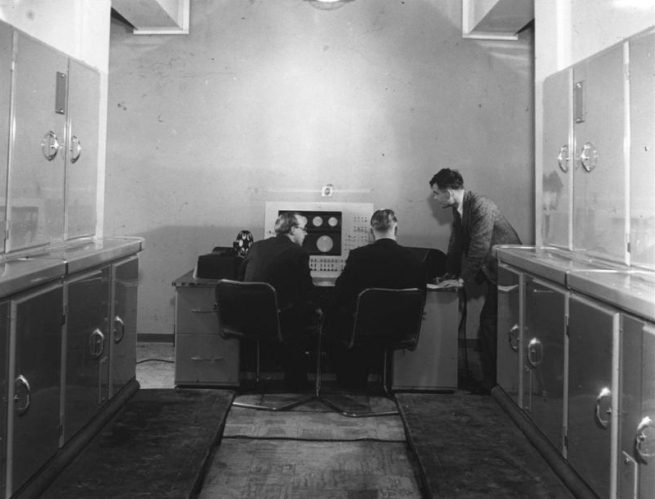 Alan Turing with two colleagues at the Ferranti Mark I computer