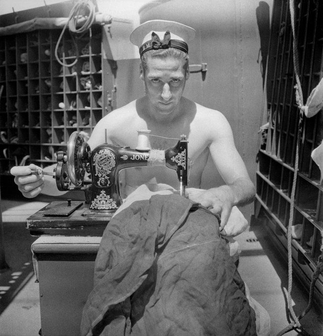 Cecil Beaton (English, 1904-1980) 'A Royal Navy sailor on board HMS Alcantara uses a portable sewing machine to repair a signal flag during a voyage to Sierra Leone' March 1942