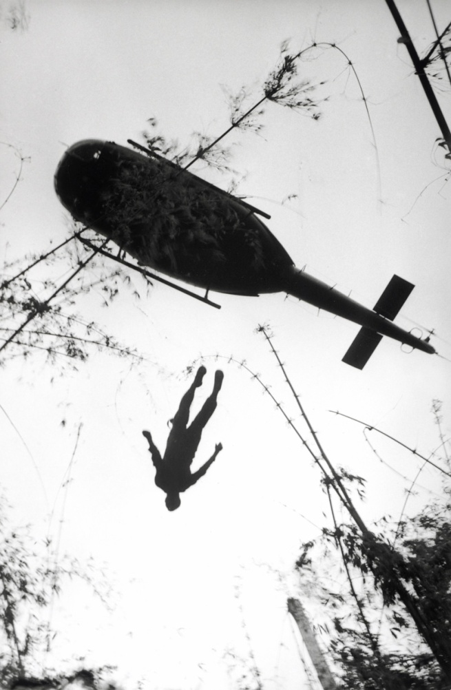 Henri Huet, French (1927-1971) 'The body of an American paratrooper killed in action in the jungle near the Cambodian border is raised up to an evacuation helicopter, Vietnam' 1966