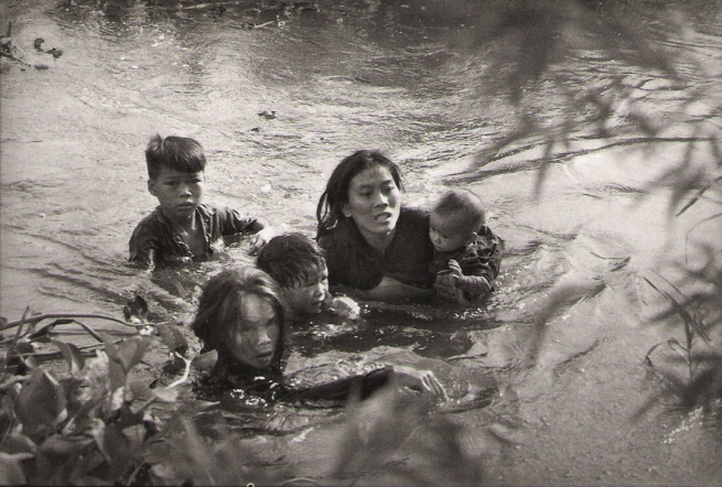 Sawada Kyoichi. 'Mother and children wade across river to escape U.S. bombing. Qui Nhon, South Vietnam' September 1965