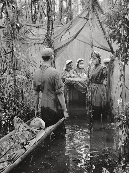 Vo Anh Khanh. 'A Cambodian guerrilla is carried to an improvised operating room in a mangrove swamp in this Viet Cong haven on the Ca Mau Peninsula' 1970