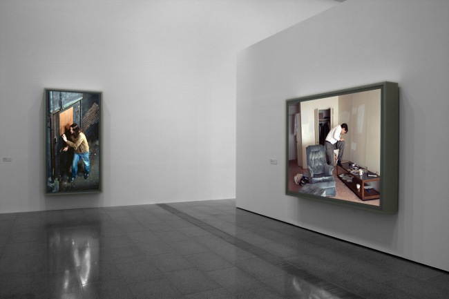 Installation view of 'Jeff Wall Photographs' at NGV Australia showing, at left, 'Doorpusher' 1984, and at right, 'Polishing' 1998