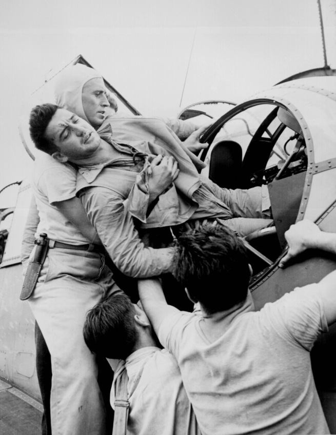 Lt. Wayne Miller. 'Crewmen lifting Kenneth Bratton out of turret of TBF on the USS SARATOGA after raid on Rabaul' November 1943