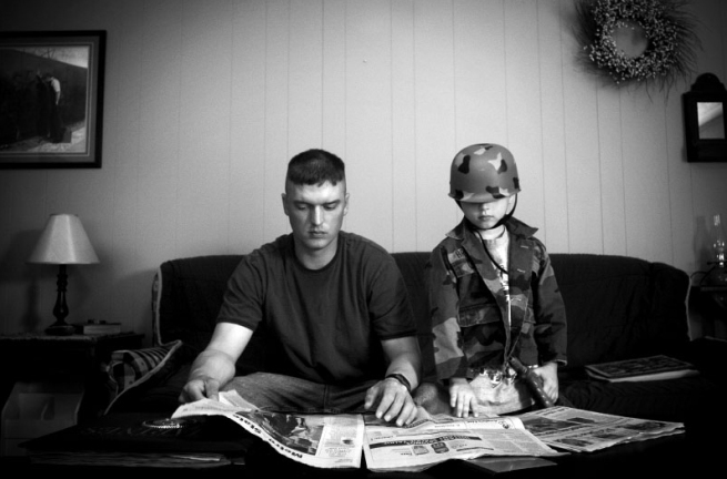 Andrea Bruce. 'Untitled [A father home on leave reading the newspaper with his son, who wears his dad's helmet]' 2006