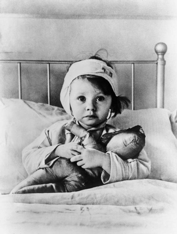 Cecil Beaton. 'Eileen Dunne, aged three, sits in bed with her doll at Great Ormond Street Hospital for Sick Children, after being injured during an air raid on London in September 1940' 1940