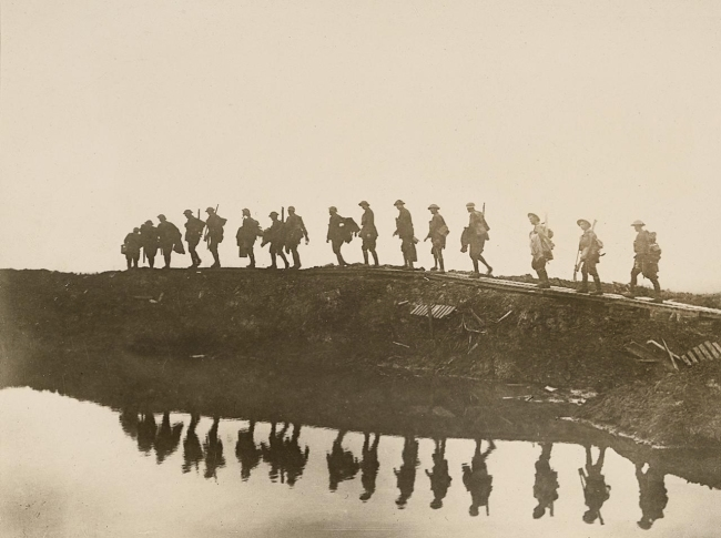 Frank Hurley (Australian, 1885-1962) 'Supporting troops of the 1st Australian Division walking on a duckboard track' 1917
