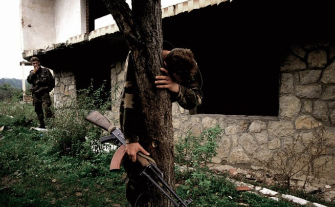 Ron Haviv (American, b.1965) 'A Bosnian soldier stands on what is believed to be a mass grave outside his destroyed home. He was the sole survivor of 69 people' 1995