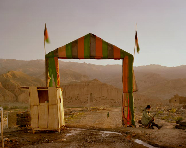 Simon Norfolk. 'Victory arch built by the Northern Alliance at the entrance to a local commander's headquarters in Bamiyan. The empty niche housed the smaller of the two Buddhas, destroyed by the Taliban in 2001' 2001