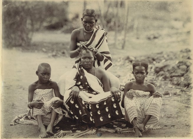 Unidentified photographer. 'Dressing hair. Women of the E. Coast. Africa' Tanzania, early twentieth century