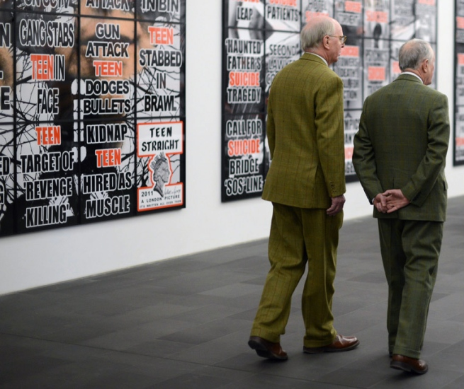 The British artists George Passmore (L) and Gilbert Prousch (R) pass in front of one of their art work 'London Pictures'