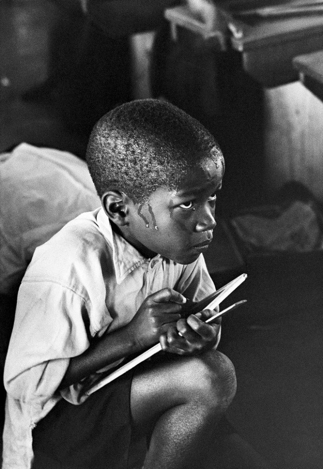Ernest Cole (1940 - 1990) 'Earnest boy squats on haunches and strains to follow lesson in heat of packed classroom' 1960-1966