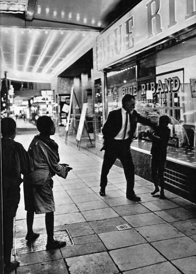 "Ernest Cole (South African, 1940-1990) '""Penny, baas, please baas, I hungry…"" This plaint is part of nightly scene in Golden City, as black boys beg from whites. They may be thrown a coin or, as here, they may get slapped in the face' 1960-1966"