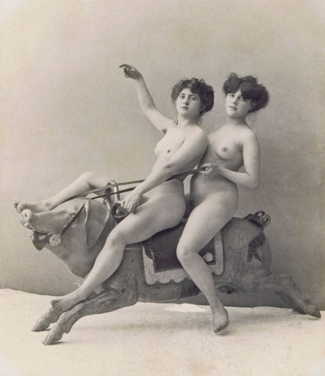 Photographer unknown. 'Two women on a carousel Pig' c. 1900