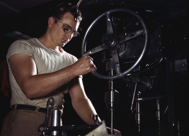 Alfred Palmer. 'An employee in the drill-press section of North American's huge machine shop runs mounting holes in a large dural casting, in Inglewood, California, in October of 1942' October 1942