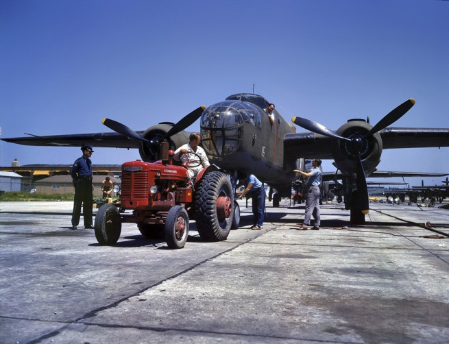 Alfred Palmer. 'B-25 bomber plane at North American Aviation being hauled along an outdoor assembly line. Kansas City, Kansas.' October 1942
