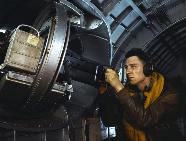 Alfred Palmer. 'Hitler would like this man to go home and forget about the war. A good American non-com at the side machine gun of a huge YB-17 bomber is a man who knows his business and works hard at it' May 1942