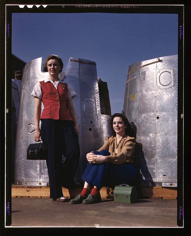 Alfred Palmer. 'Two assembly line workers at the Long Beach, Calif., plant of Douglas Aircraft Company enjoy a well-earned lunch period, Long Beach, Calif. Nacelle parts of a heavy bomber form the background' October 1942