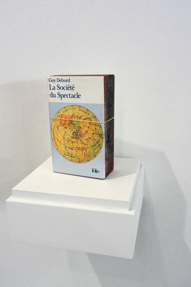 Claire Fontaine. 'La société du spectacle brickbat' 2006 (installation view)