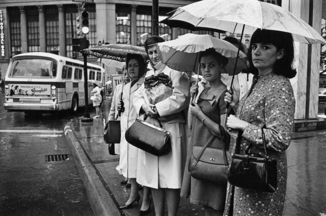 Enrico Natali. 'Women waiting at a bus stop in the rain, Detroit, 1968' 1968