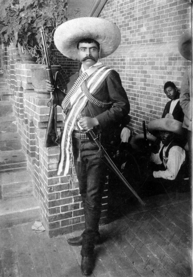Hugo Brehme (?) (German, 1882-1954, active in Mexico) 'Emiliano Zapata with Rifle, Sash, and Saber, Cuernavaca' June 1911