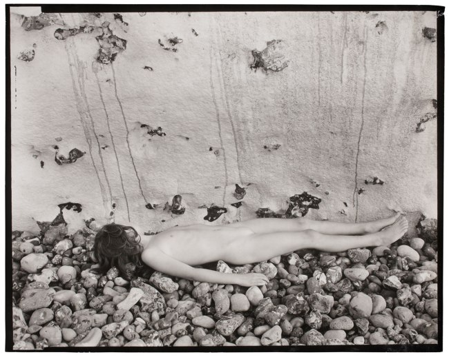 Guy Bourdin. 'Untitled' (Child lying on stones) 1953-57
