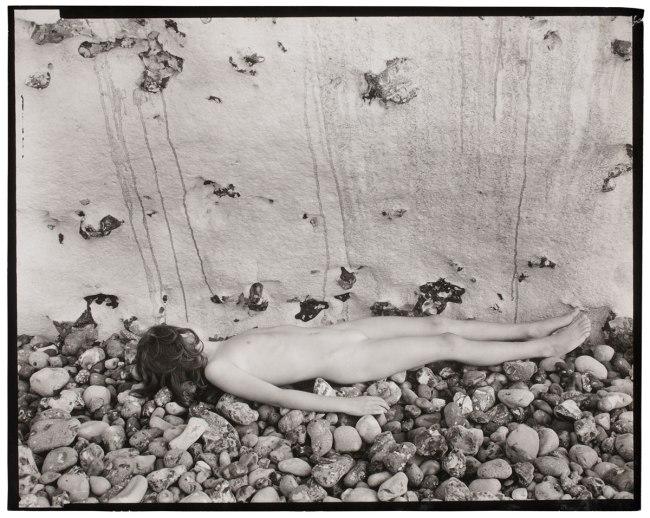 Guy Bourdin. 'Untitled' (Child lying on stones) 1953-57