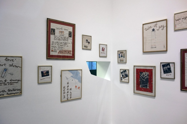 David McDiarmid Installation photograph of early works including 'Secret Love art show, poster' (1976, far left), 'Secret Love' (1976, top centre left), 'Ken's Karate Klub' (1976, centre below left) and 'Tube of joy' (1976, above right) - all from the 'Secret Love' series, 1976 except KKK